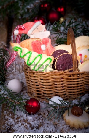 christmas cookies in a basket with red and white christmas balls and a wooden santa claus