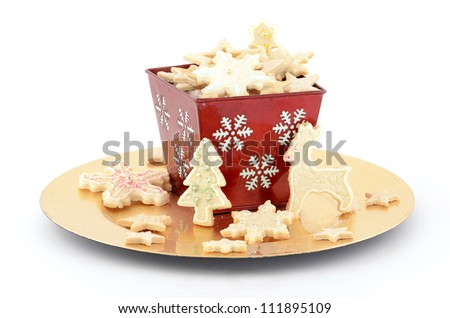 Christmas cookies in red basket on gold plate with white background