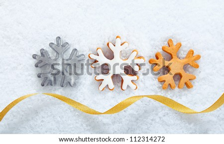 Christmas cookies in the shape of ornate snowflakes lying in a line on snow with a decorative gold ribbon for your seasonal greeting