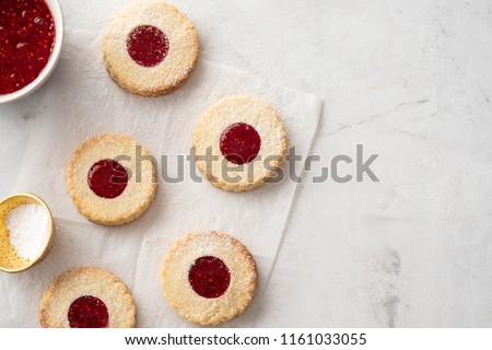 Christmas cookies. Linzer cookies with raspberry jam on white table background. Traditional Austrian biscuits filled. Top view and copy space #1161033055