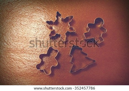 Christmas cookies making, cookie cutters on the pastry brown background. Photo is filtered.   #352457786