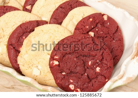 Christmas cookies. red velvet and white chocolate macadamia nut cookies in a ceramic bowl with a wooden tabletop background. Selective focus.