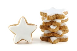 Christmas cookies, stack of cinnamon stars, a single one standing, in Germany called zimtsterne, close up isolated on white background