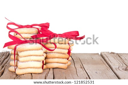 Christmas cookies stacked and tied with red bow on rustic wooden planks