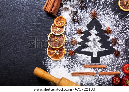 Christmas cooking: fir tree made from flour on a dark table, ingredients for baking and dried fruits on dark background, top view
