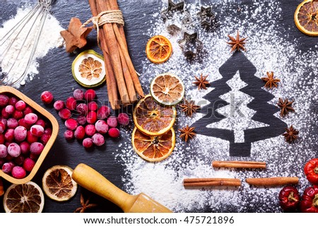 Christmas cooking: fir tree made from flour on a dark table, ingredients for baking, frozen cranberry and dried fruits on dark background, top view