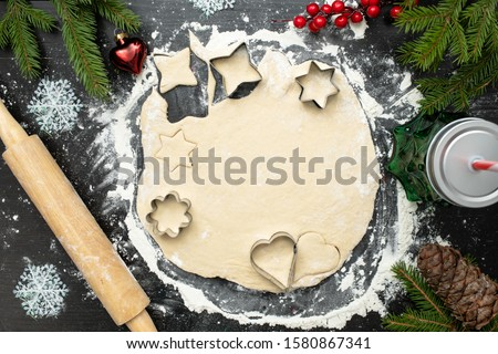 Christmas cooking, ginger cookies or biscuits , raw dough with cutters and rolling pin on dark table decorated with spruce branches, holy berries Stock photo ©