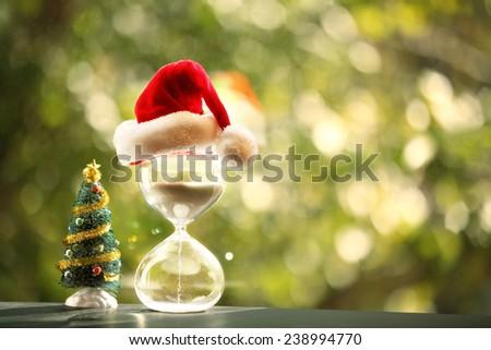 Christmas countdown. Modern Hourglass and Christmas tree -- sand trickling through the bulbs of a crystal sand glass.