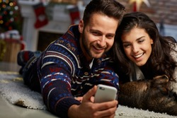 Christmas couple at home in Winter. Happy young couple lying on floor using smart phone at home with dog at Christmas time. Christmas tree and fireplace in background.