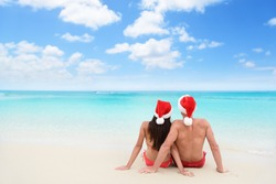 Christmas couple in love lying down relaxing on white sand beach sun tanning in tropical travel destination during winter holidays. Back view of young adults wearing santa hat.