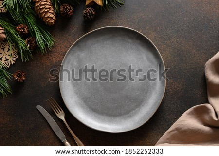Christmas cozy table setting with empty grey plate and wooden decor on brown table. Rustic home style. Top view, flat lay. Foto d'archivio ©