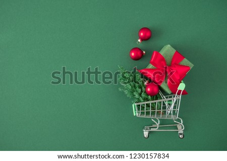 Christmas creative minimal composition. Shopping cart and Xmas red gift, red decorations, fir tree branches on green background. Christmas, New Year, winter concept. Flat lay, top view, copy space