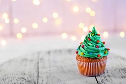 Christmas cupcake with sparkler and lights on background