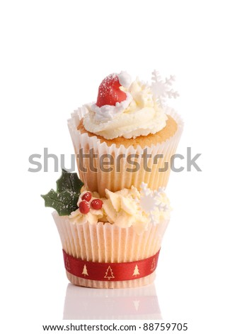 Christmas cupcakes decorated with santa hats and snowflakes on white background