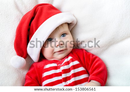 christmas cute smiling baby boy lying on soft plaid, beautiful funny infant in Santa's hat