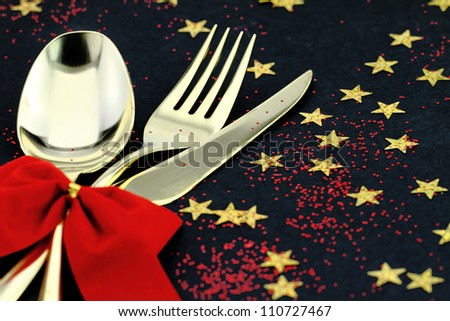 Christmas cutlery. Spoon, fork and knife stacked up on a starry background