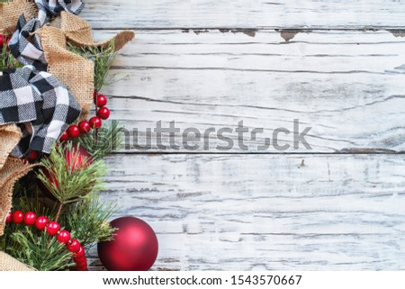Christmas Day background with holiday trimmings of pine tree branches, ornaments, black and white buffalo check ribbon, burlap and red bead garland. Top view with copy space available.