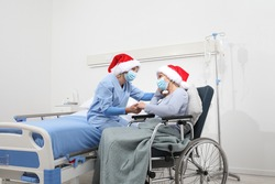 Christmas day isolated in hospital room with coronavirus, nurse take comfort elderly woman celebrating xmas wearing red caps and surgical protective medical masks