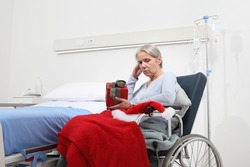 Christmas day isolated in hospital room with coronavirus, sad and pensive elderly woman on wheelchair with red hat and gift near bed, concept of solitude, isolation and quarantine