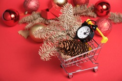 christmas decor and black small alarm clock in a mini shopping trolley on a red background, new year shopping concept