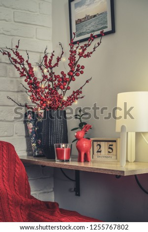 Christmas decor at home. Red toy elk, candle and vase with decorative twigs on shelf closeup. The PHOTO in FRAME on the wall made by me.