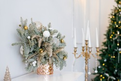 Christmas decor in a classic living room or Spruce branches in gold vases with toys and a gold candlestick on the dresser