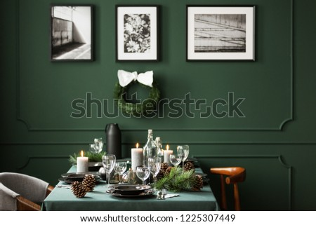 Christmas decor in stylish dining room interior with communal table with plates, wine glasses and candles, real photo with christmas wreath and posters in black frames on empty green wall