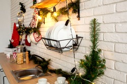 Christmas decor in the kitchen, preparing for the celebration. Lights of garlands, plates, incandescent lamps in loft style. Christmas tree, kitchen utensils. New year's eve, Christmas. House interior