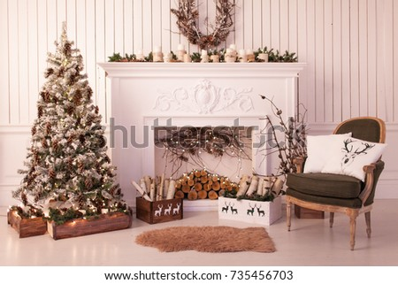 Christmas decor of a bright stylish living room with a vintage armchair, fireplace, Christmas tree and candles
