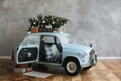 Christmas decorated classic car. A vintage car decorated for New year holidays loaded with festive gifts. Christmas retro car decorated loaded with Christmas tree and presents
