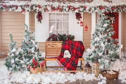 Christmas decorated house and yard. Studio decoration in New Year style. Snow covered courtyard of a wooden house or cottage with red decore accents. Backdrop for photographer