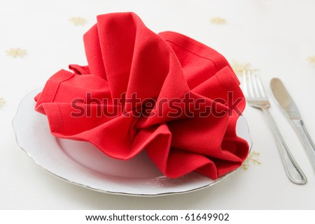 Christmas decorated table for a menu with red folded napkin.