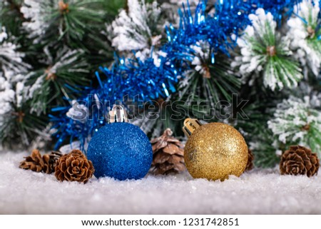 Christmas decoration blue and gold balls with tree an blue tinsel in snow