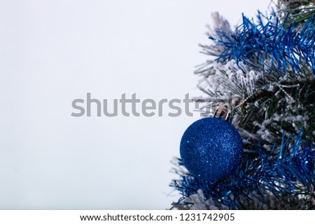 Christmas decoration blue and silver balls in a tree with tinsel and pinecone in snow