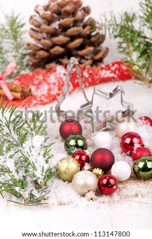 christmas decoration, christmas cookie cutters (star and christmas tree) with red, green, and white christmas balls with fir branches, white snowflakes