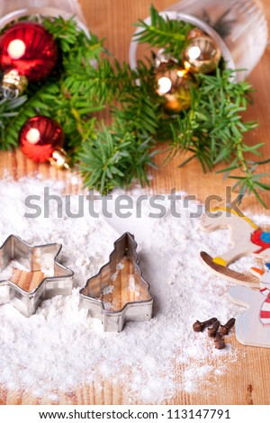christmas decoration, christmas cookie cutters with flour (star and christmas tree) on wooden table, in background red and gold christmas balls with fir branches