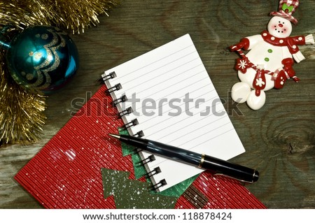 Christmas decoration Christmas items on an old wooden surface. The spiral note book is for festive free writing space