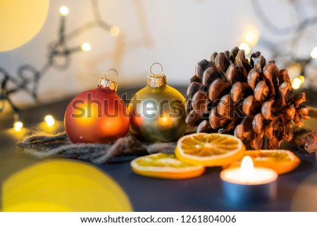 christmas decoration closeup of a pinecone with candels and a christmas ball, christmas string lights with blurry lightballs in the background, christmas feeling