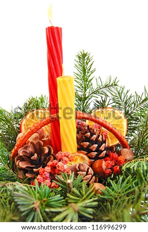 Christmas decoration: fir sprig,candles, cones, berries and dried orange