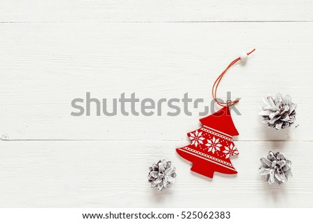 Christmas decoration fir- tree and pine cones on white boards. Top view. Space for text.