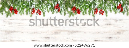 Christmas decoration. Floral holidays banner. Evergreen tree branches with red berries on wooden background #522496291