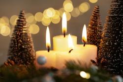 Christmas decoration four burning candle lights at christmas eve on dark background.
