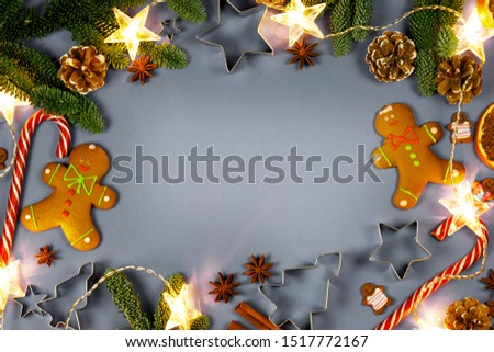 Christmas decoration frame. Gingerbread cookies, candy canes, fir tree branches and cones, star garland decorations on gray background with copy space