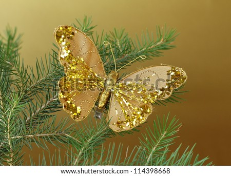 Christmas decoration (golden butterfly) on the branches of fir