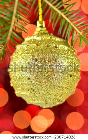 christmas decoration, golden Christmas ball hanging on spruce twig against bokeh background