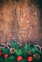 Christmas decoration. Green branches with ornaments on an old blank wooden background. Copyspace, vertical portrait.