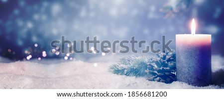 Photo of  christmas decoration idyll in deep snow on blurred blue background, beautiful natural christmas background with shiny candlelight and advertising space