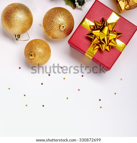 Christmas decoration isolated white. Red and golden gift boxes with three golden ball, and floral ornament. Top view. Square composition.