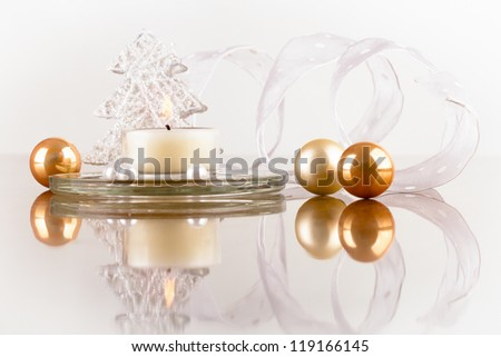 Christmas decoration of candles, artificial pearls, balloons and ribbons on shiny white surface