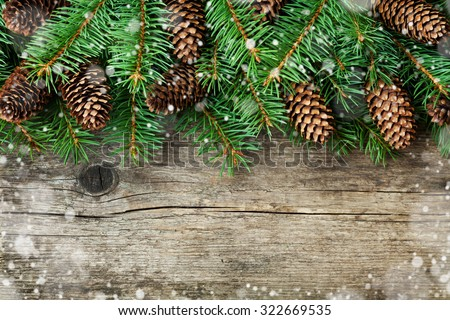 Christmas decoration of fir tree and conifer cone on texture wood background, magic snow effect, top view